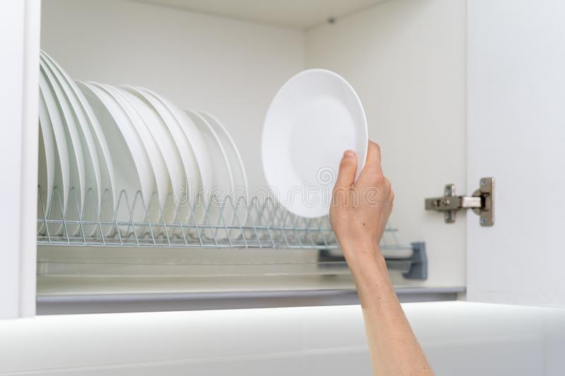 Woman holding clean and white plate near dishware in kitchen cabinet. Cropped view of woman holding clean and white plate near dishware in kitchen cabinet stock images
