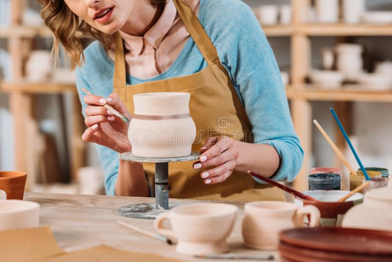 Cropped view of woman painting ceramic jug. In pottery workshop stock image