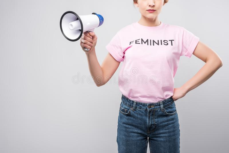 Cropped view of woman in pink feminist t-shirt holding megaphone,. Isolated on grey stock photography
