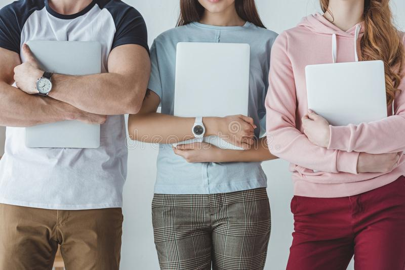 Cropped view of young students holding. Laptops royalty free stock images