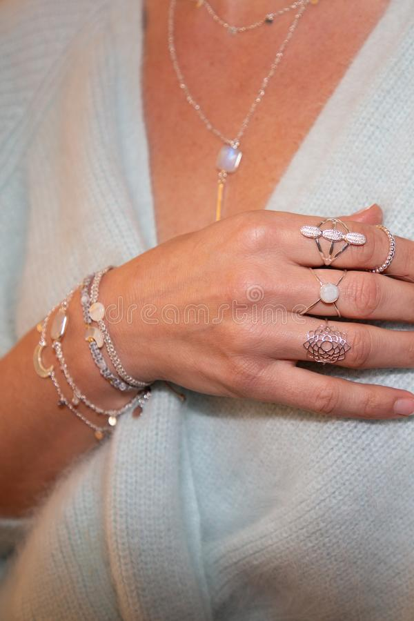 Cropped view of the young woman with a silver necklace  bracelets and rings royalty free stock photography