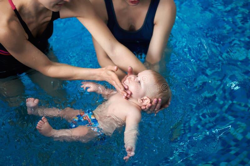 Cropped widok dwa kobiety próbuje ostrożnie utrzymywać dziecka na wodzie Śliczny spokojny małego dziecka lying on the beach na je obrazy stock
