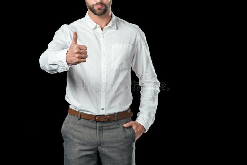 cropped widok odizolowywający na czerni biznesmen w białym koszulowym pokazuje kciuku up, zdjęcia royalty free