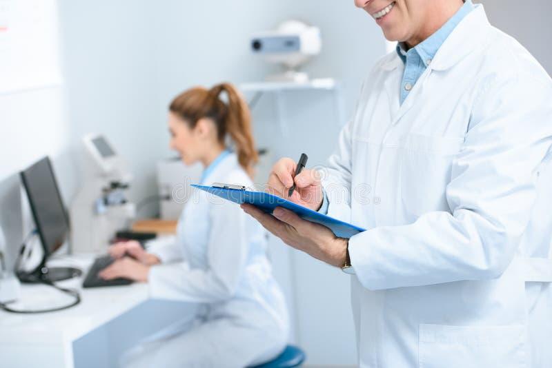 cropped widok pisze diagnozie męski optometrist podczas gdy kolega używa z komputerem obrazy stock