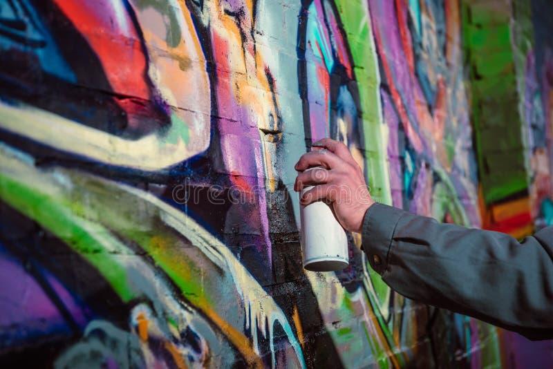 cropped widok uliczni artysty obrazu graffiti z aerosolową farbą na ścianie zdjęcia stock