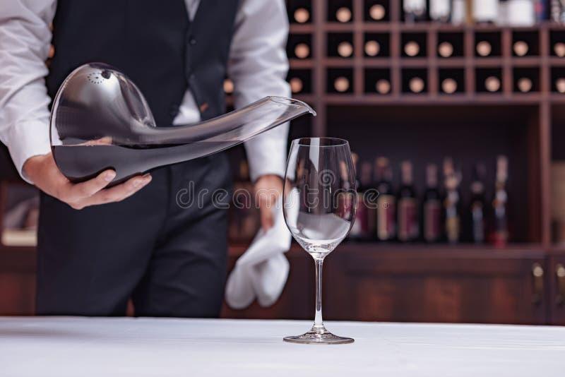 Cropped widoku sommelier dolewania czerwone wino od dekantatoru w szkło przy stołem zdjęcia royalty free