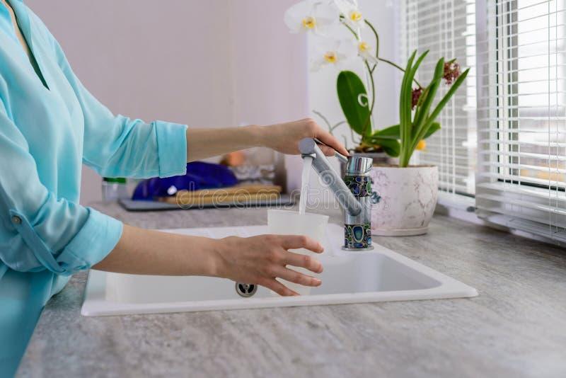 Cropped wizerunek żeńskie ręki z filiżanką nalewa filtrującą wodę kranową w kuchni obraz royalty free