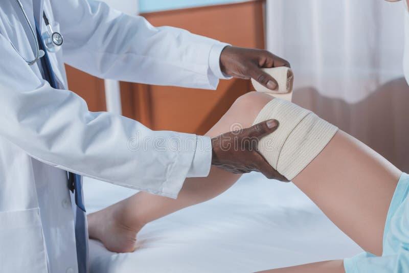 Cropped wizerunek amerykanin afrykańskiego pochodzenia lekarki kładzenie na elastycznym bandażu obrazy stock