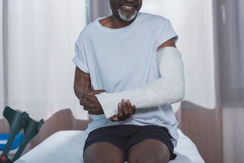 Cropped wizerunek amerykanina afrykańskiego pochodzenia pacjent z łamaną ręką obraz royalty free