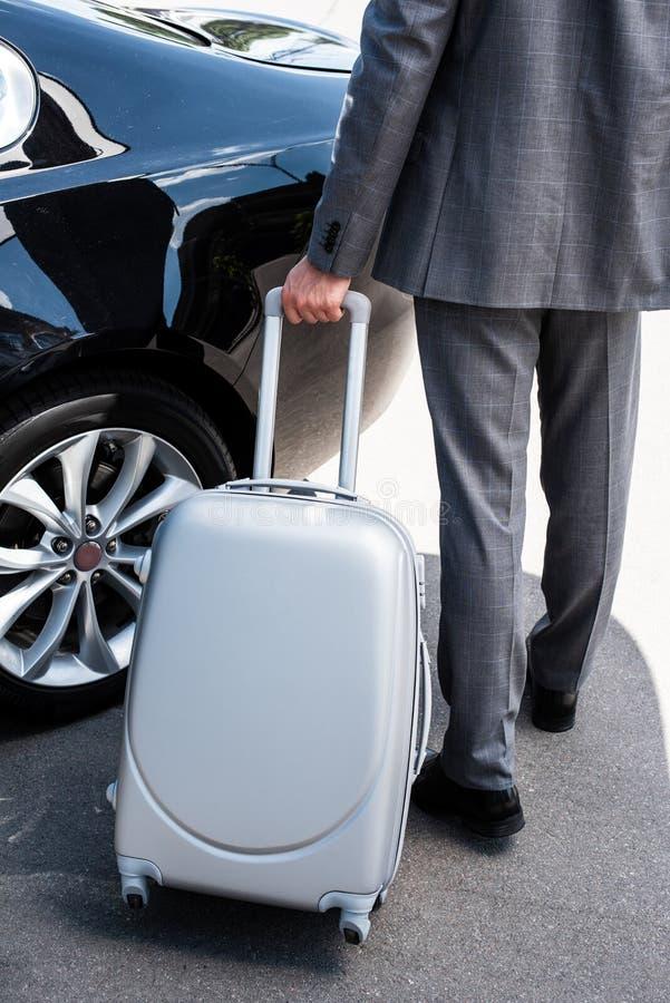 cropped wizerunek biznesmena przewożenie toczył torbę blisko samochodu obrazy stock