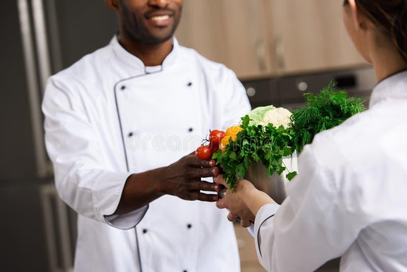 cropped wizerunek daje pucharowi z warzywami amerykanin afrykańskiego pochodzenia kolega szef kuchni zdjęcie stock