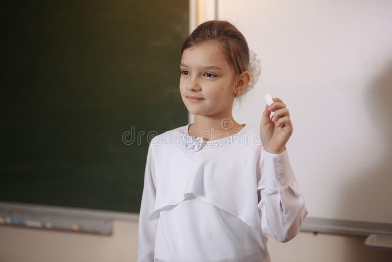 Cropped wizerunek dziewczyny ` s ręki writing na zielonym chalkboard w dziecinu obraz royalty free