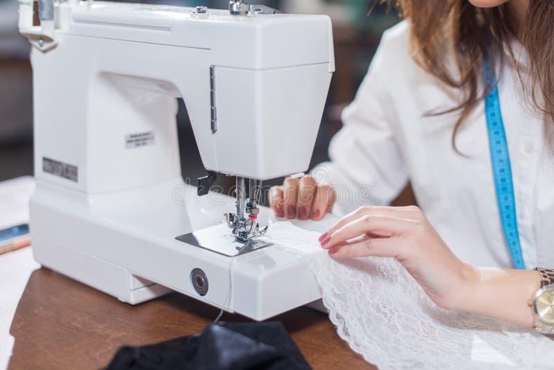 Cropped wizerunek kobieta krawczyny zaszywania grzywny koronka z szwalną maszyną siedzi w dressmaking studiu fotografia stock