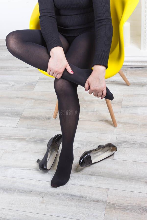 Cropped wizerunek kobieta masuje ona w szpilkach męczył nogi zdjęcia stock