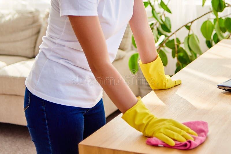 Cropped wizerunek kobieta w białej koszula i żółtych ochronnych gumowych rękawiczkach czyści w domu i wyciera pył na drewnianym t obraz royalty free