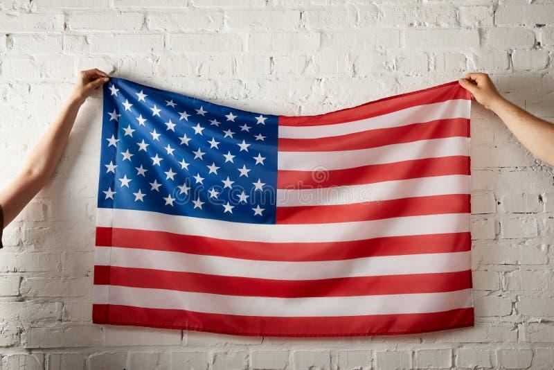cropped wizerunek mężczyzna i kobiety mienia flaga amerykańska przeciw ściana z cegieł zdjęcia royalty free
