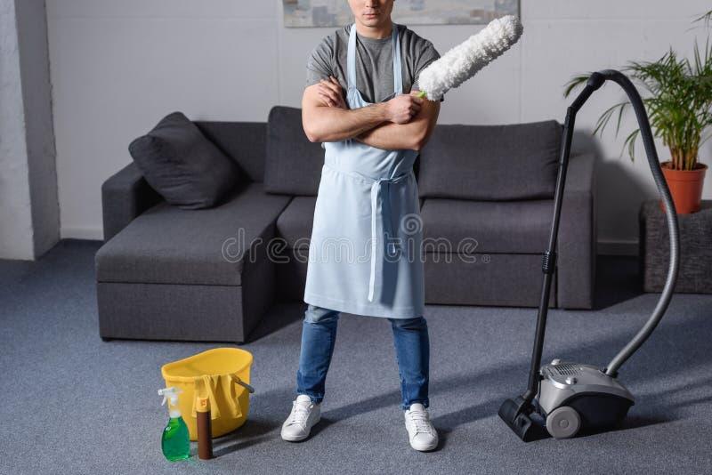 cropped wizerunek mężczyzna pozycja i mienia muśnięcie dla czyści pyłu obrazy stock