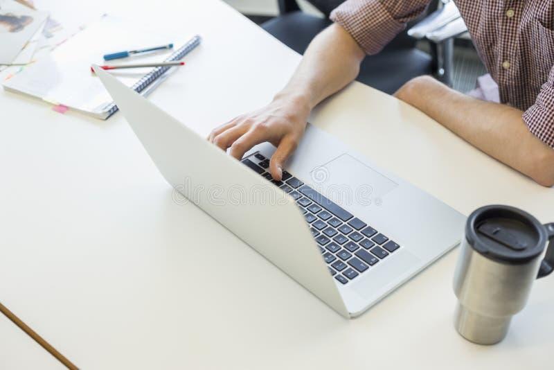 Cropped wizerunek mężczyzna używa laptop przy biurkiem w kreatywnie biurze zdjęcie stock