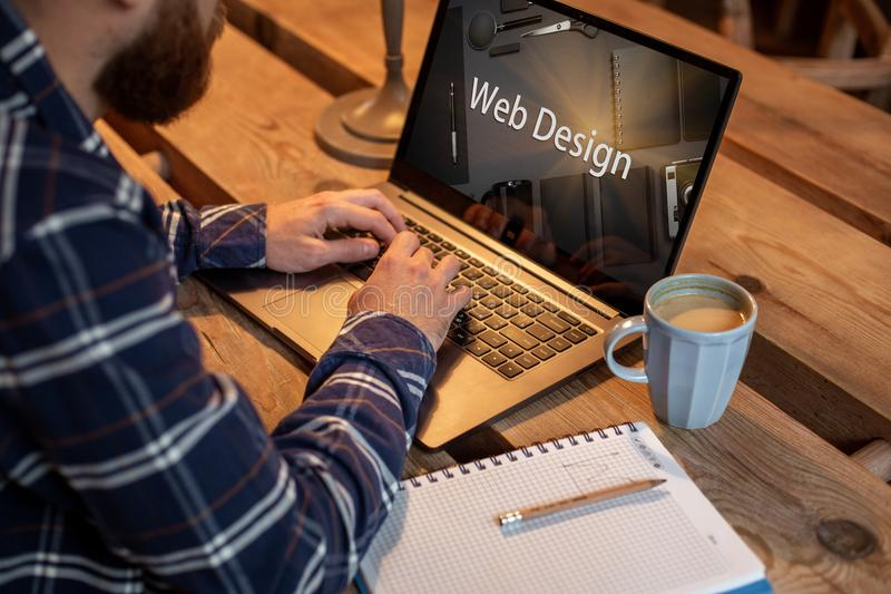 Cropped wizerunek młody człowiek pracuje na jego laptopie w sklep z kawą, tylni widok biznesowy mężczyzna wręcza ruchliwie używa  fotografia stock