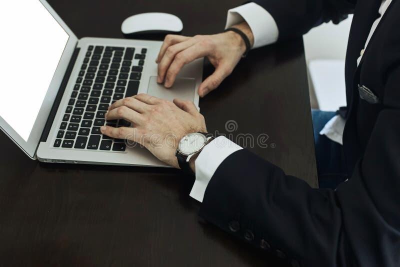 Cropped wizerunek młody człowiek pracuje na jego laptopu tylni widoku biznesowy mężczyzna wręcza ruchliwie używa laptop przy biur zdjęcia stock