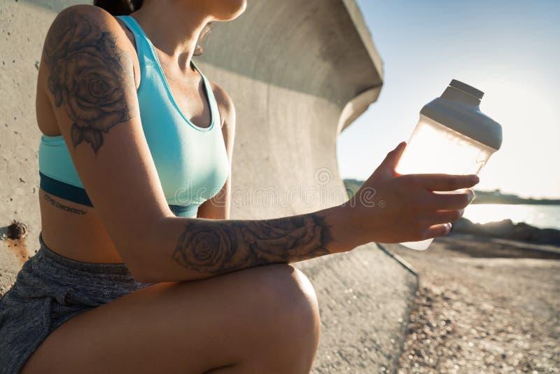 Cropped wizerunek młodzi sprawności fizycznej kobiety odpoczywać i obsiadanie obrazy stock
