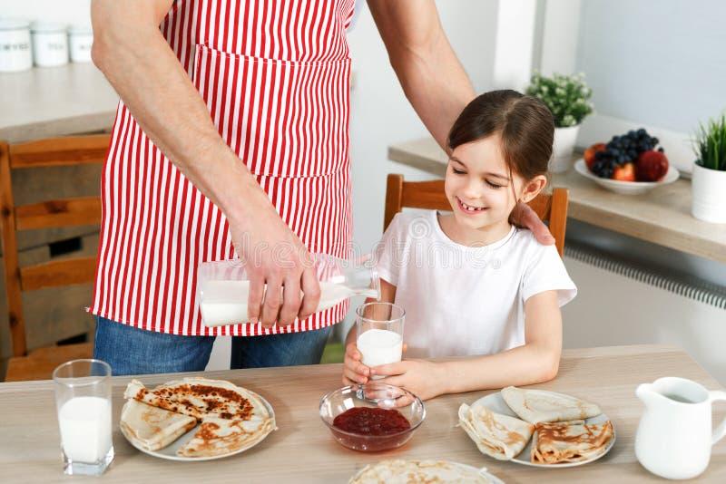 Cropped wizerunek ostrożny ojciec jest ubranym fartucha, nalewa świeżego mleko w szkle dla jego córki, piec wyśmienicie bliny fotografia stock