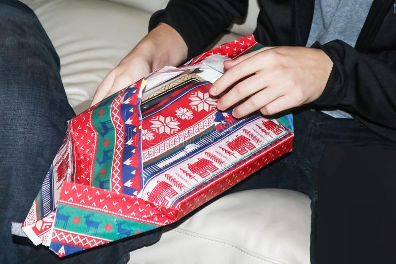 Cropped young man sitting on leather sofa opening Christmas gift in colorful wrapping paper royalty free stock photos