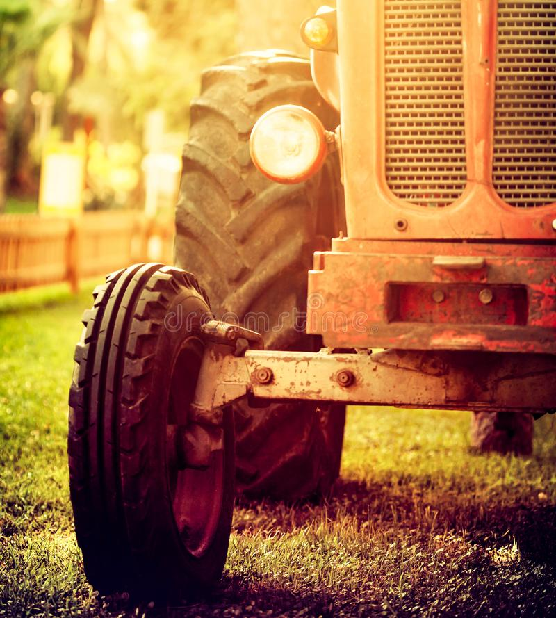 Old vintage red tractor standing on a farm field at sunset. Croppped photo of old vintage red tractor standing on a farm field at sunset stock photo
