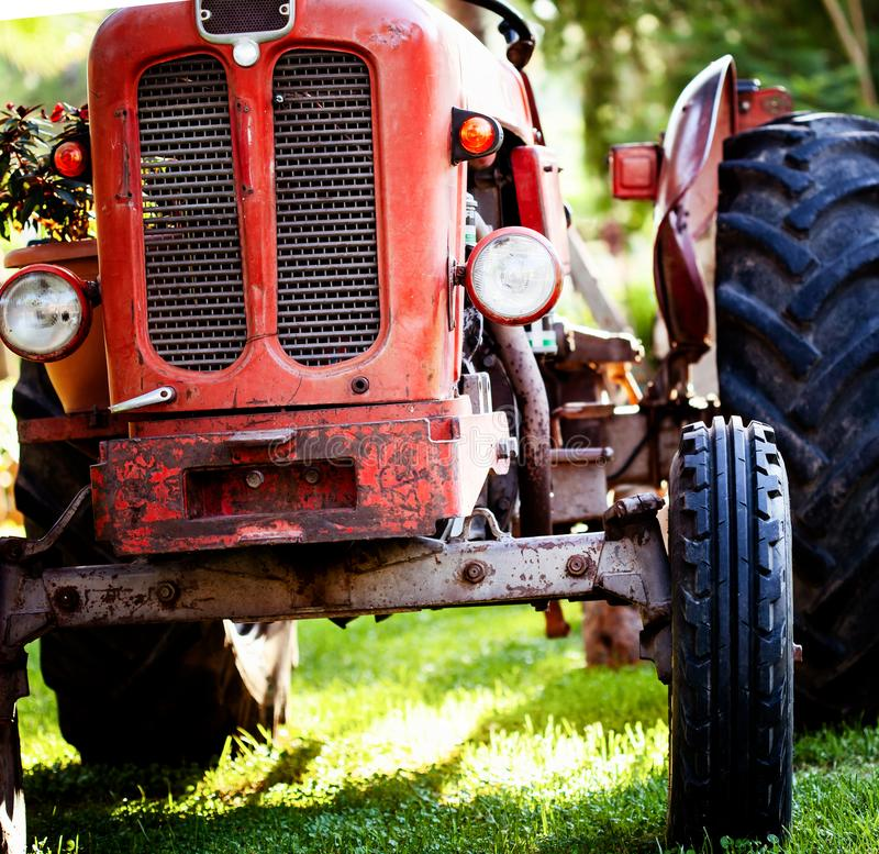 Old vintage red tractor standing on a farm field at sunset. Croppped photo of old vintage red tractor standing on a farm field at sunset royalty free stock photography