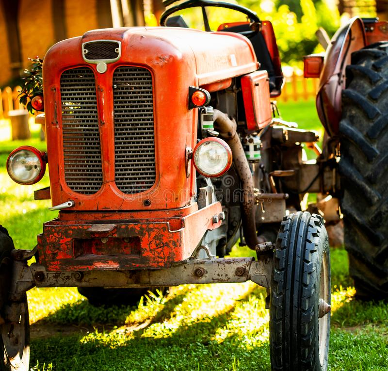 Old vintage red tractor standing on a farm field at sunset. Croppped photo of old vintage red tractor standing on a farm field at sunset stock images