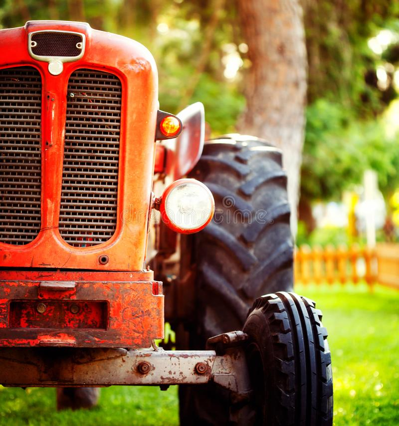 Old vintage red tractor standing on a farm field at sunset. Croppped photo of old vintage red tractor standing on a farm field at sunset royalty free stock photo