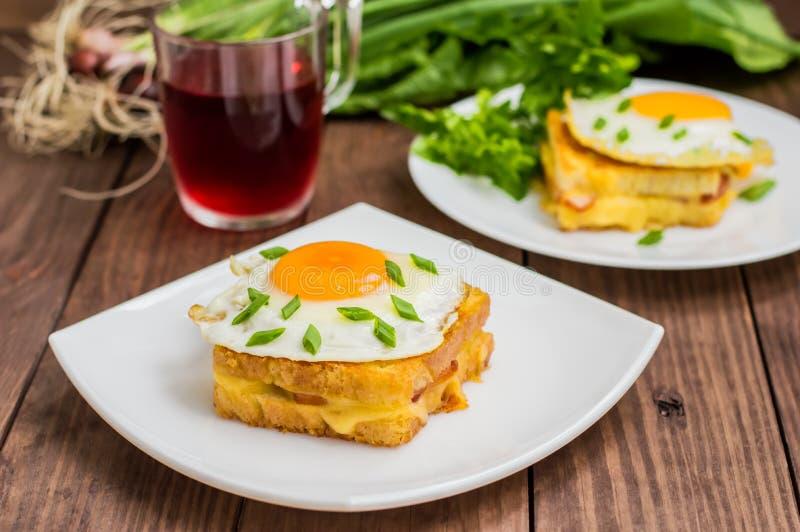 Croque-Madame, ein französisches Sandwich mit Grüns und Beerensaft für Frühstück Holztisch Beschneidungspfad eingeschlossen Nahau stockfotos