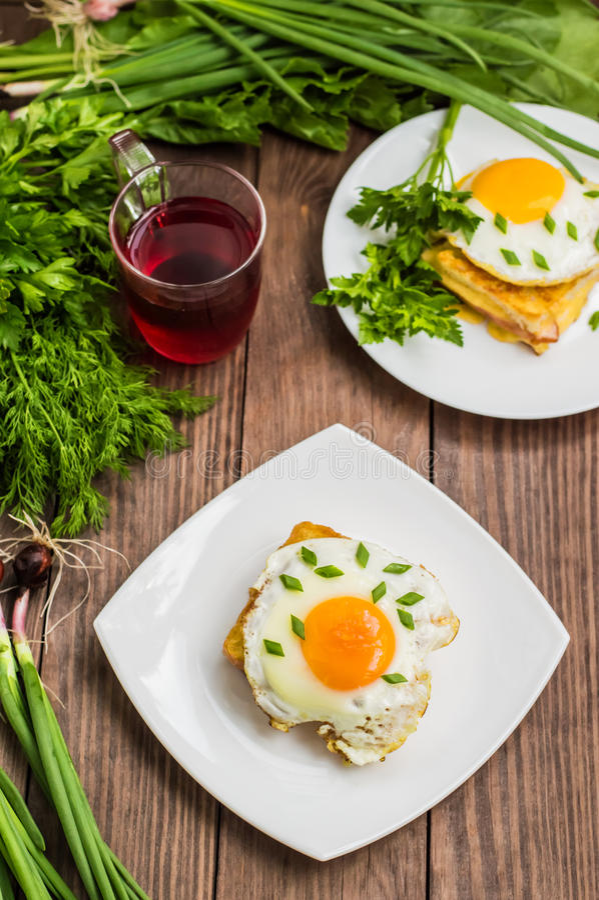Croque-Madame, ein französisches Sandwich mit Grüns und Beerensaft für Frühstück Holztisch Beschneidungspfad eingeschlossen Nahau stockfoto