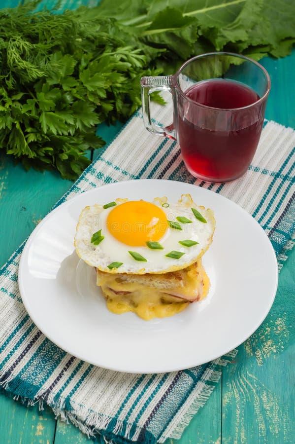 Croque-Madame, ein französisches Sandwich mit Grüns und Beerensaft für Frühstück Holztisch Beschneidungspfad eingeschlossen Nahau lizenzfreie stockfotografie