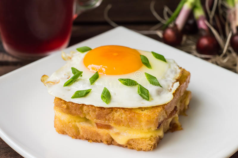 Croque-Madame, ein französisches Sandwich mit Grüns und Beerensaft für Frühstück Holztisch Beschneidungspfad eingeschlossen Nahau stockbilder