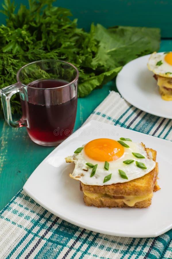 Croque-Madame, ein französisches Sandwich mit Grüns und Beerensaft für Frühstück Holztisch Beschneidungspfad eingeschlossen Nahau lizenzfreies stockfoto