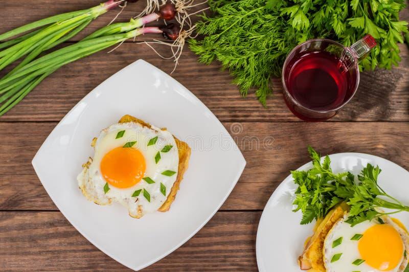 Croque-Madame, ein französisches Sandwich mit Grüns und Beerensaft für Frühstück Holztisch Beschneidungspfad eingeschlossen Nahau lizenzfreie stockbilder