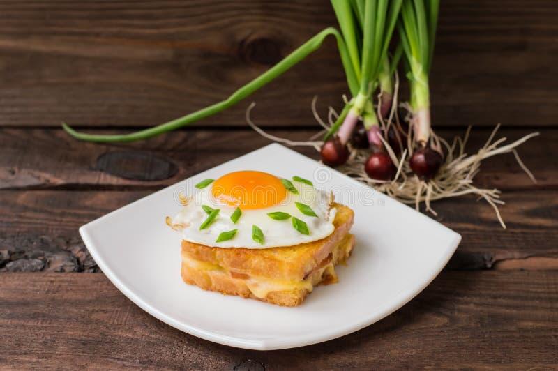 Croque-Madame, un sandwich français avec des verts et jus de baie pour la table en bois de petit déjeuner Vue supérieure Plan rap image libre de droits