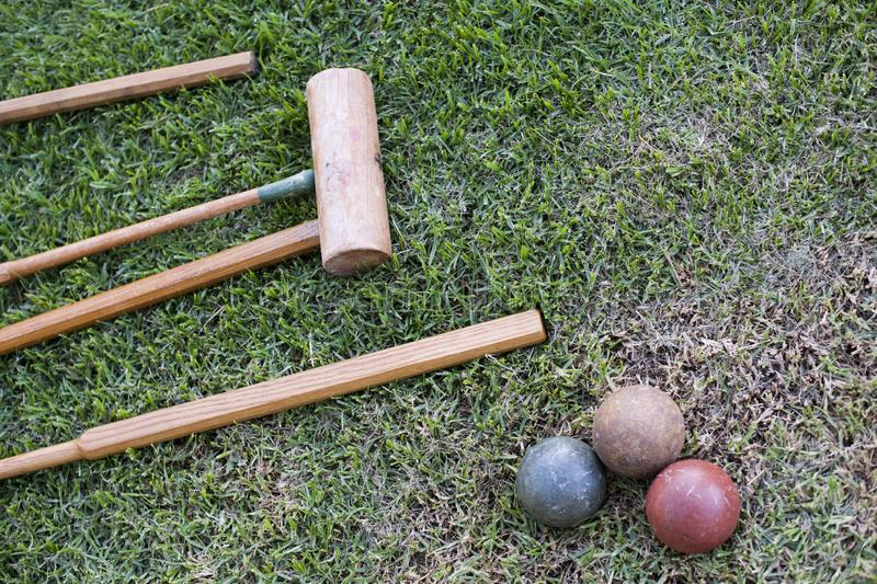 A croquet set lie on a lawn of grass with three balls royalty free stock photography