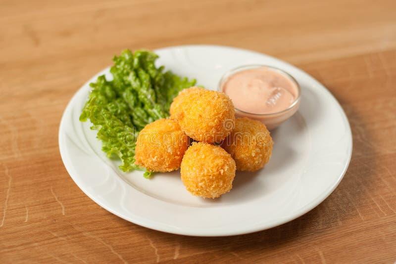 Croquettes délicieuses de fromage d'un plat avec de la sauce photos libres de droits