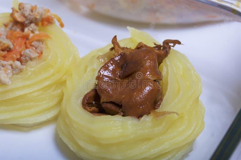 Croquettes des pommes de terre avec le bourrage du fromage, des champignons et de la viande hachée Ils s'étendent dans une plaque image libre de droits