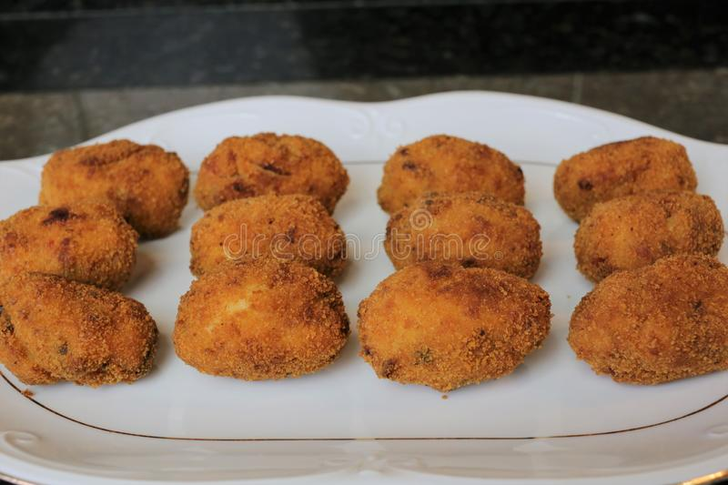 Croquettes fried in olive oil. That can be filled with many ingredients such as meat, fish, prawns or ham. The croquettes are in a white plate on a black stock photo