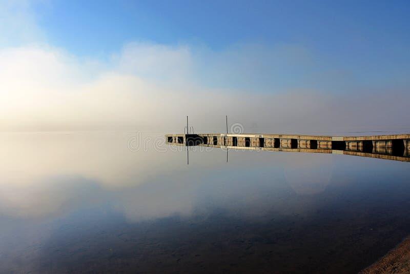 Croquis de début de la matinée par le lac brumeux Ponton de réflexion dans l'eau photographie stock libre de droits