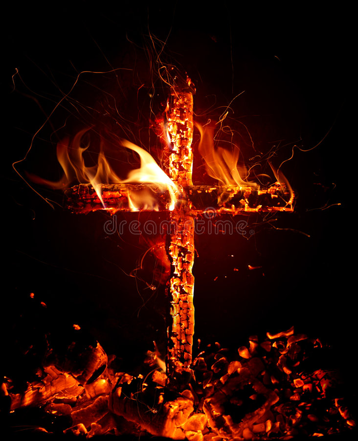 Cross. Burning cross against black background