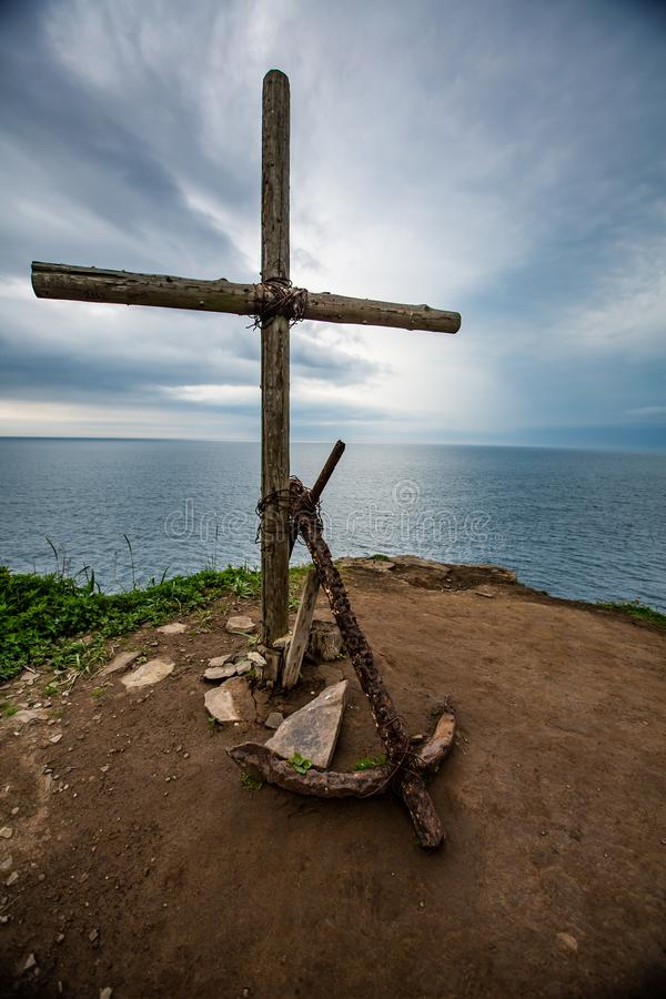 Cross and anchor on the mountain on the background of sea and sky royalty free stock photography