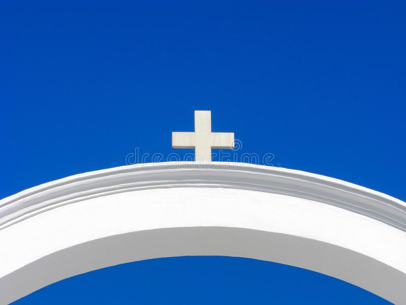 Cross on arch, blue and white, greek architecture, religion, symbols. White cross on white arch is isolated on clear blue sky. Greek architecture, Cyclades royalty free stock images