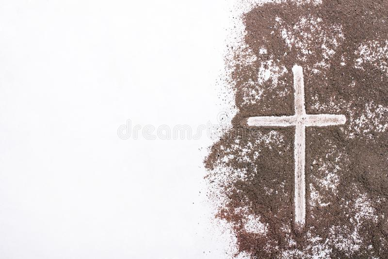 Cross and ash - Ash Wednesday. Cross and ash on white background - symbol of Ash Wednesday. Copy space stock photos