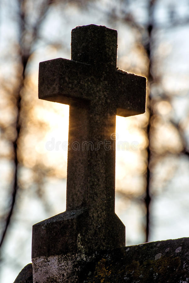 Cross in back light. At a pilgrim way in a forest stock photo
