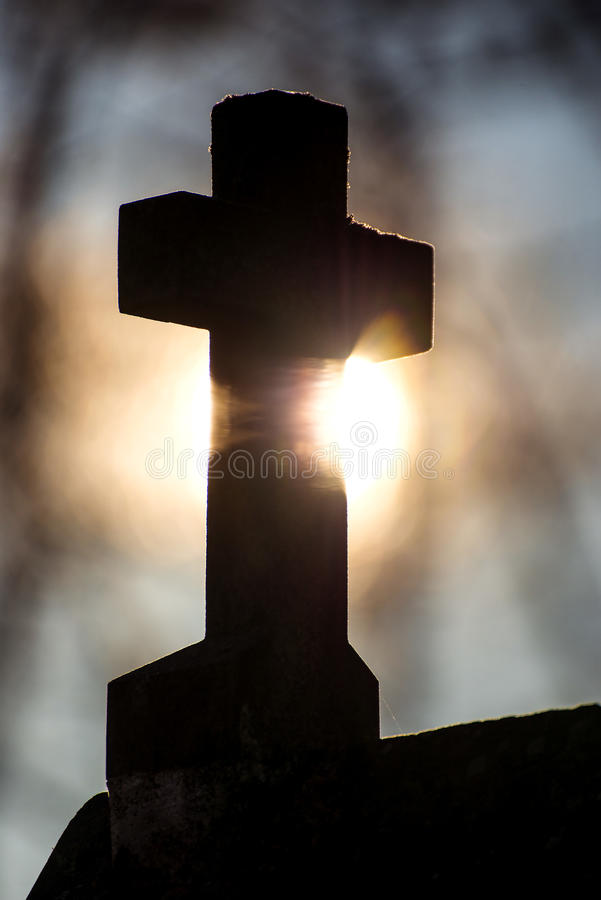 Cross in back light. At a pilgrim way in a forest stock photography