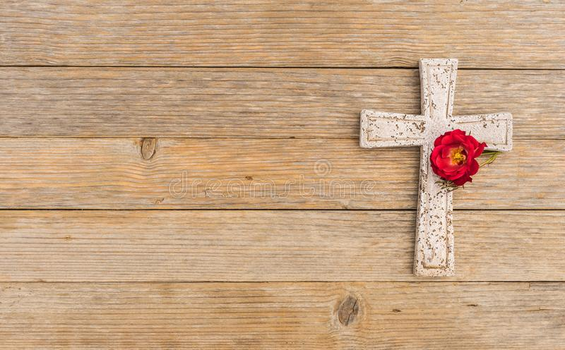 Cross background, religious christian stone cross and rose blossom on wood for death and grief concept stock images